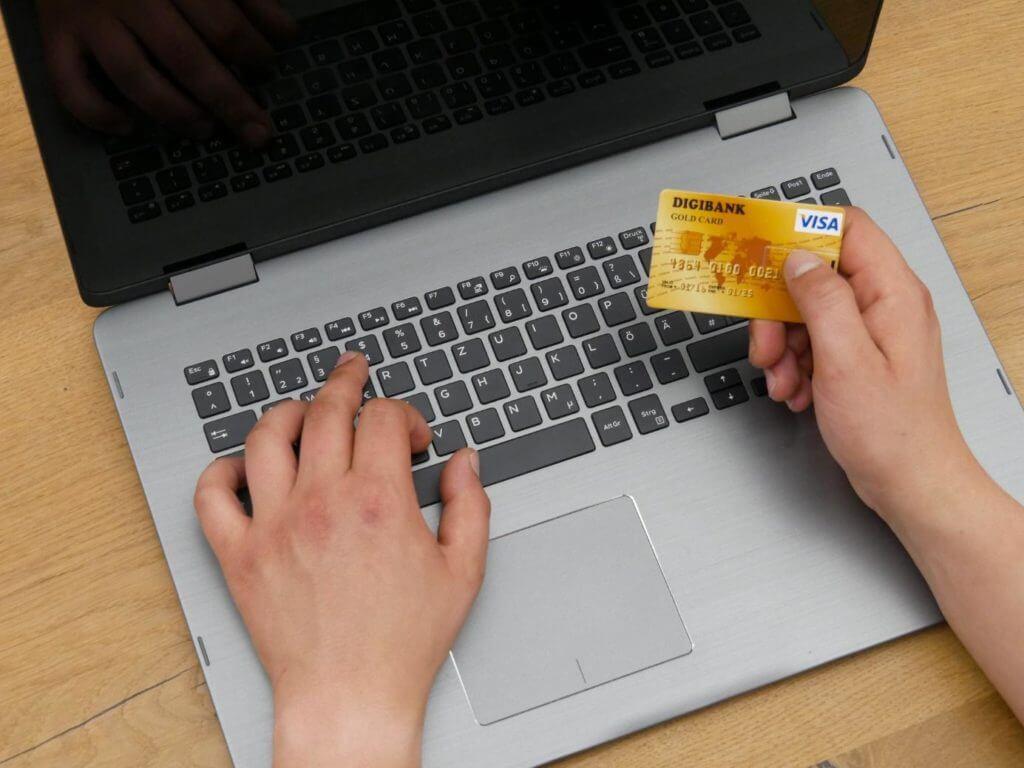 Mann hält VISA-Kreditkarte in seiner Hand und tippt auf einer Notebook-Tastatur mir schwarzem Display